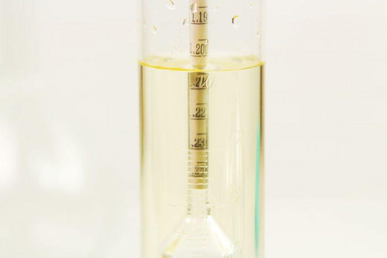 Um densímetro dentro de uma proveta com líquido transparente.