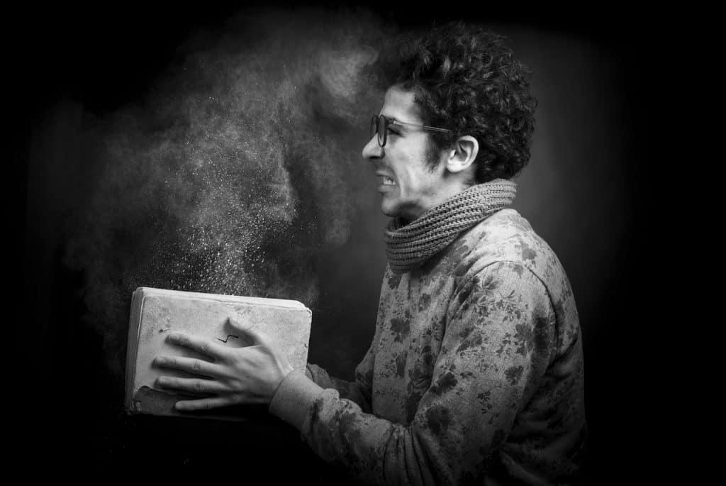 Em um cenário escuro, um homem assustado segura um livro empoeirado.