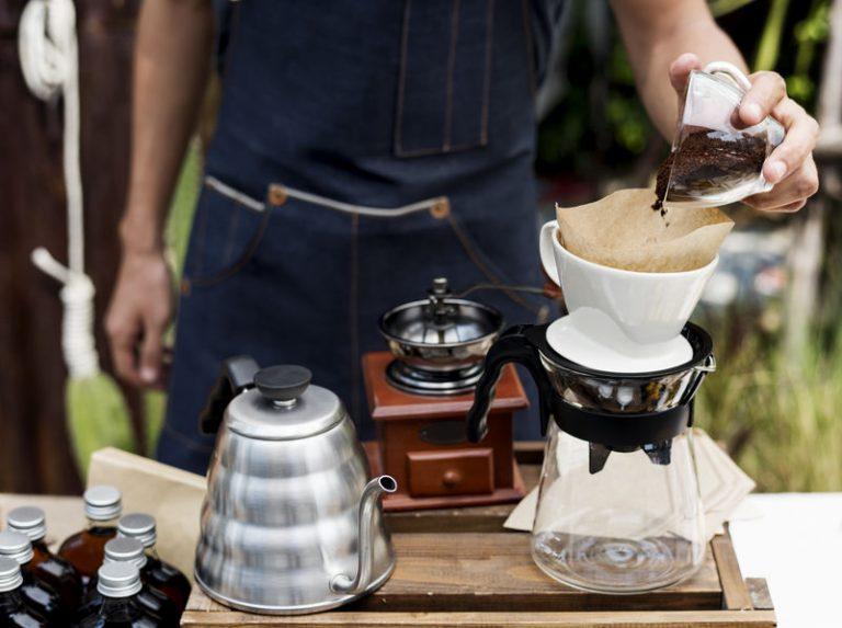 Imagem de pessoa utilizando um funil para fazer a coagem do café