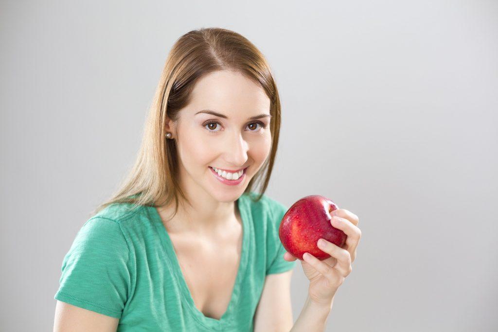 Imagem de uma mulher com uma maçã nas mãos.