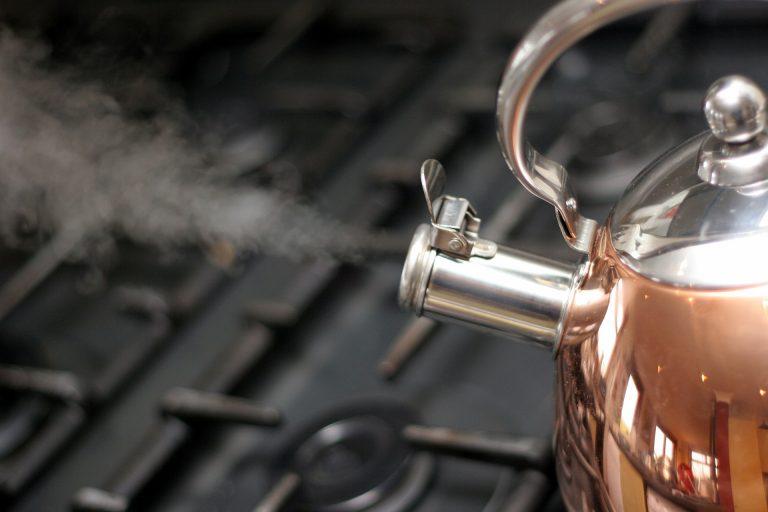 Chaleira no fogão saindo fumaça ao ferver a água.