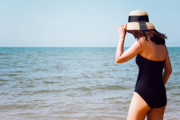 Na foto uma mulher de maiô de costas em frente para o mar.