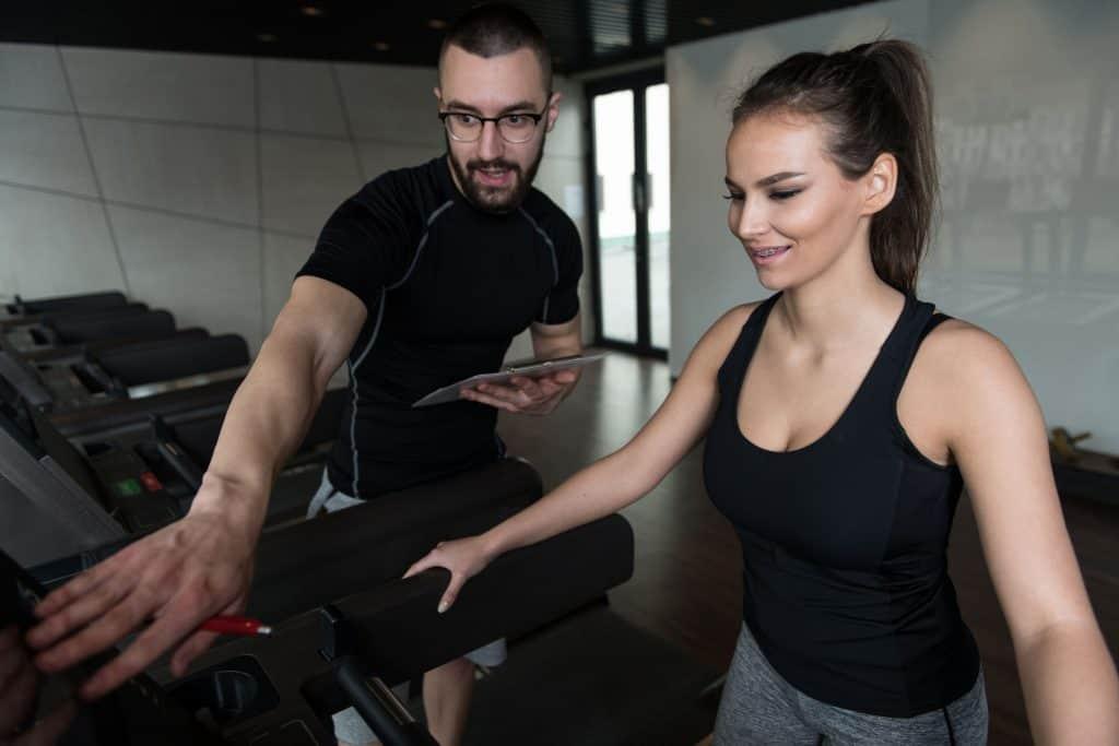 Imagem de personal trainer auxiliando aluna no exercício elíptico.