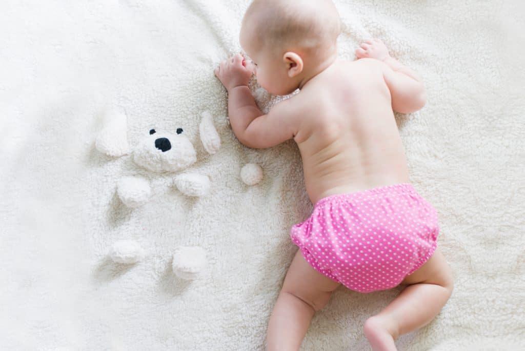 Bebê com fralda de pano rosa.