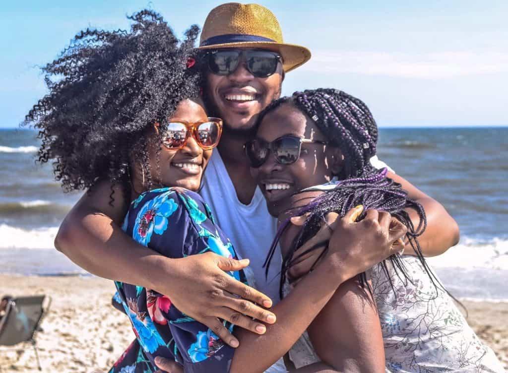 Imagem de três pessoas se abraçando.