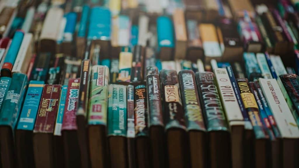 Imagem mostra foca numa fileira de livros, com o seu tombo para cima. Em sgundo plano, pelo menos outras três fileiras visíveis.