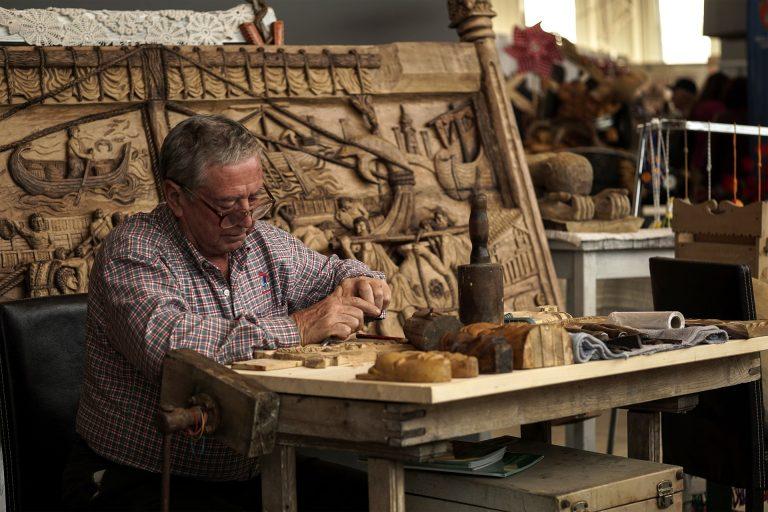 Imagem mostra um homem trabalhando com a talhadeira em madeira.