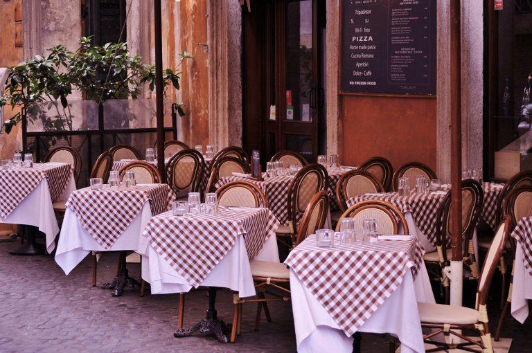 Imagem de mesas de restaurante quadradas com toalha de mesa xadrez de branco e vermelho