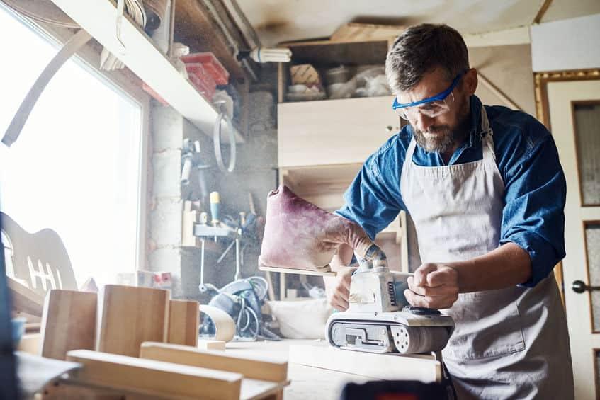Homem trabalhando em uma oficina de marcenaria com uma lixadeira de cinta.
