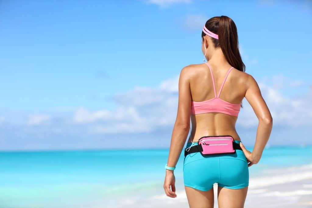 Na foto uma mulher de costas com roupas esportivas em uma praia.
