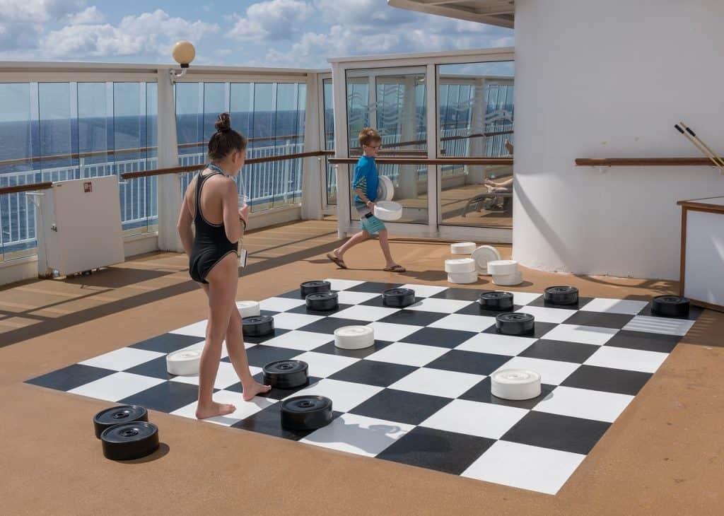 Imagem mostra duas crianças jogando em um tabuleiro de damas gigante.