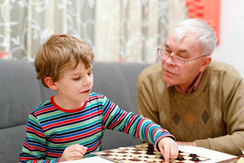 Imagem mostra avô e neto jogando damas.