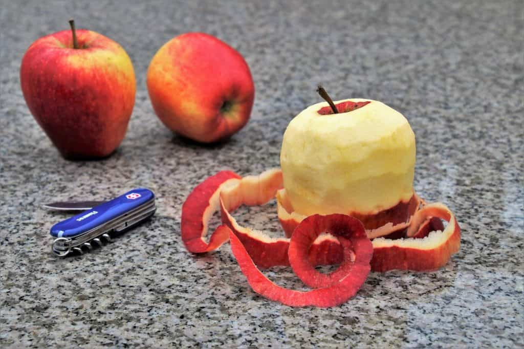 Três maçãs e um canivete em cima de mesa. Uma das maçãs está descascada.