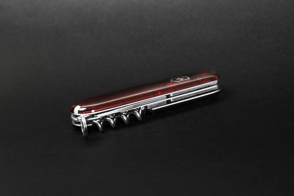 Canivete suíço fechado em um fundo preto.