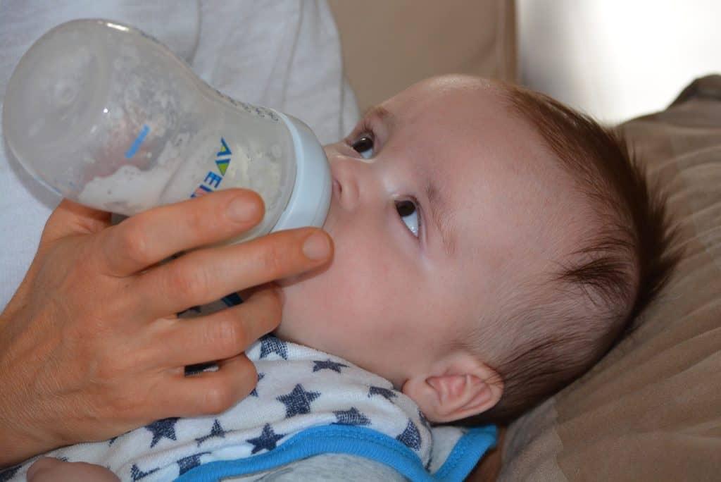 Na foto um bebê mamando em uma mamadeira.