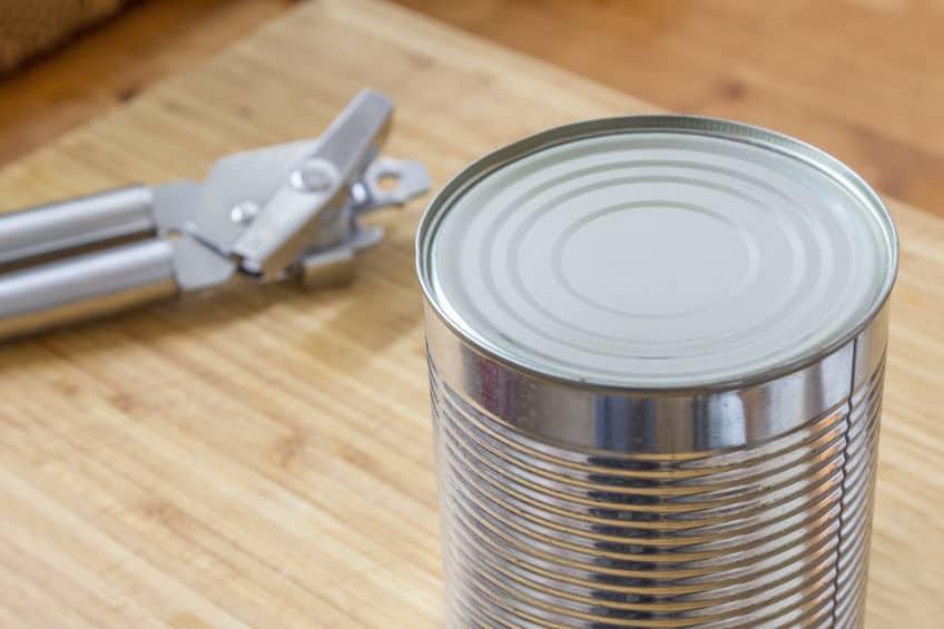 Imagem de abridor de lata e lata sobre mesa.