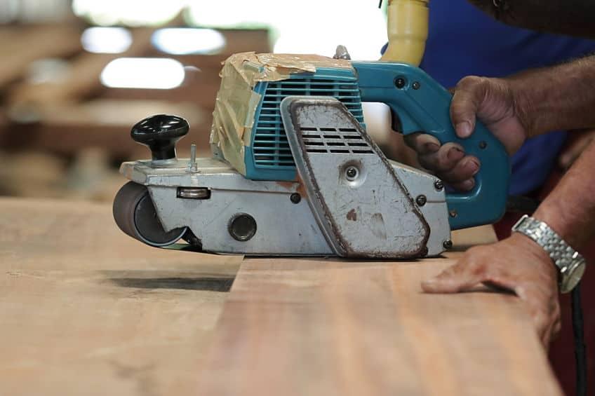 Mão de homem segurando madeira e usando uma lixadeira de cinta.