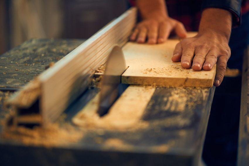 Foto de duas mãos manuseando madeira em serra circular.