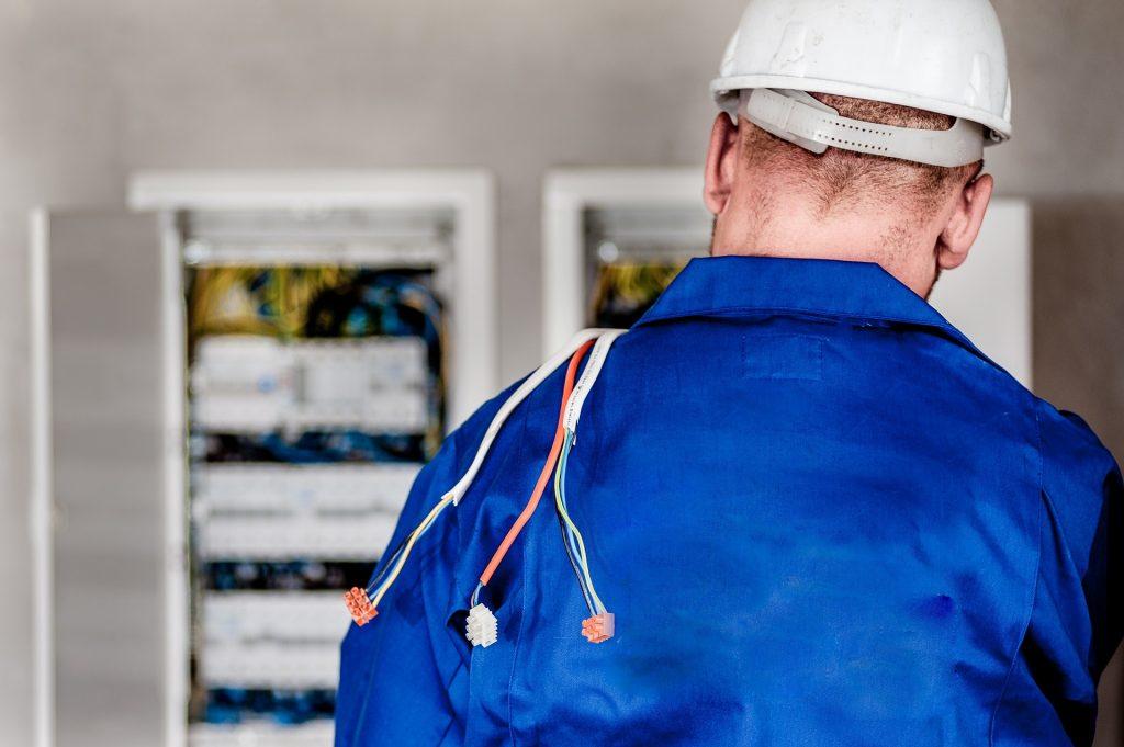 Imagem mostra um homem trabalhando em um quadro de eletricidade.
