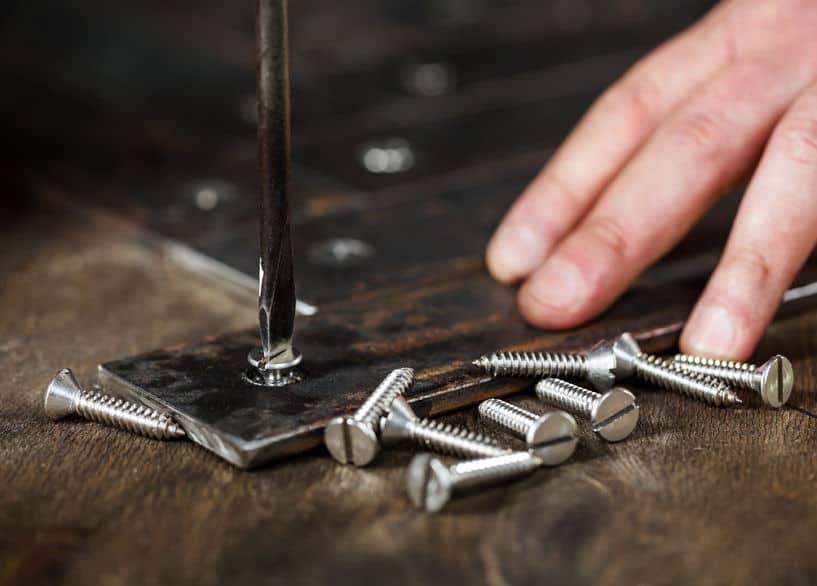 Mão de homem usando uma chave de fenda para apertar um parafuso.