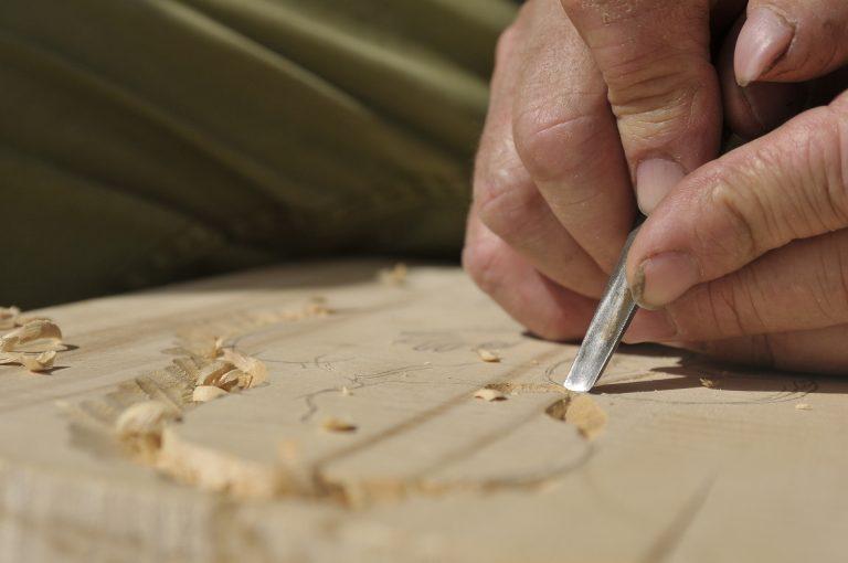 Imagem mostra uma pessoa usando uma talhadeira para esculpir madeira.