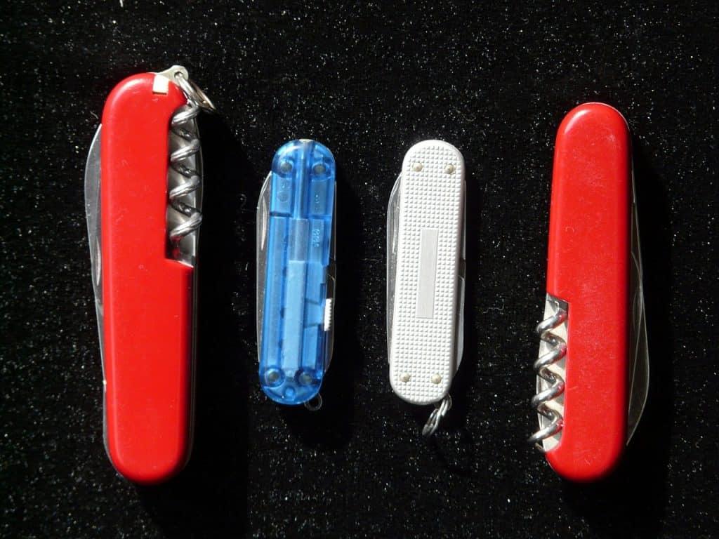 Quatro canivetes lada a lado em um fundo preto.