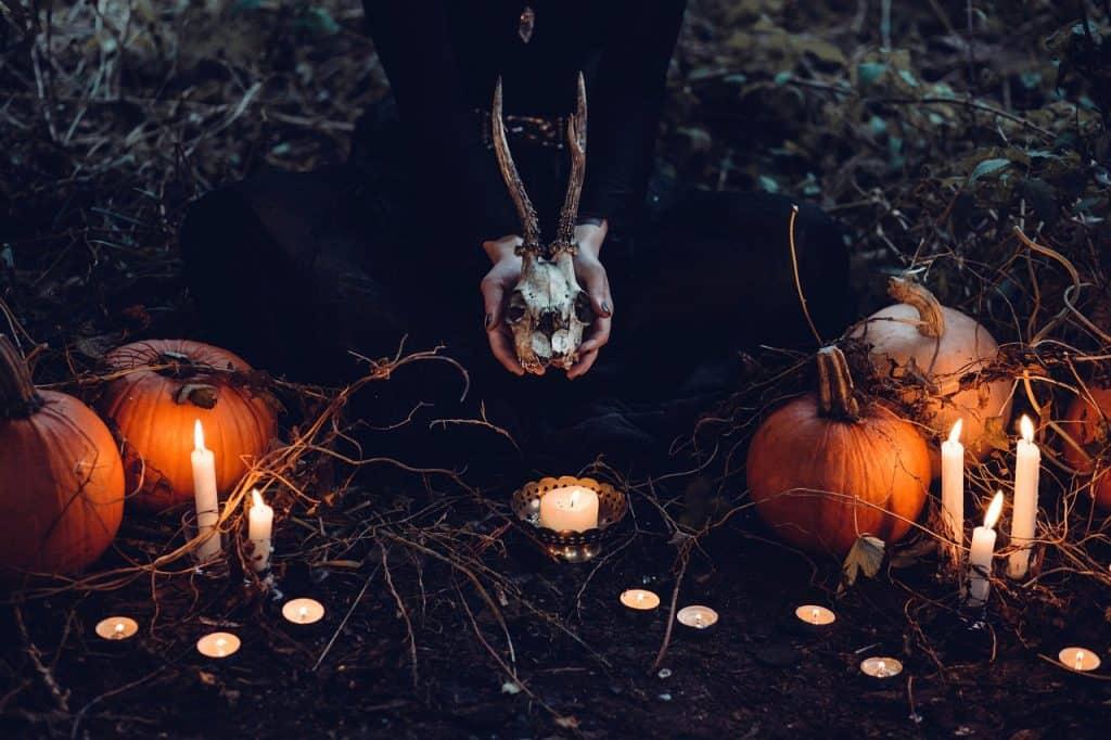 Uma pessoa de roupas negras segura um esqueleto de cabeça de bode com chifre. Ao redor existem velas acesas e abóboras. Tudo acontece de noite no meio do mato.
