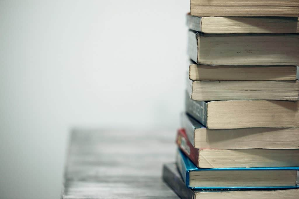 Imagem mostra uma pilha de livros, com apenas seus cortes inferiores à mostra, sob uma mesa de madeira, desfocada, em segundo plano.