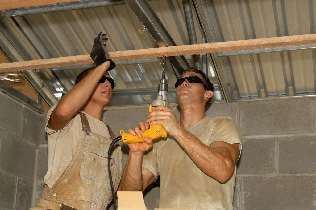imagem com profissionais utilizando a furadeira, para perfurar uma barra de madeira.