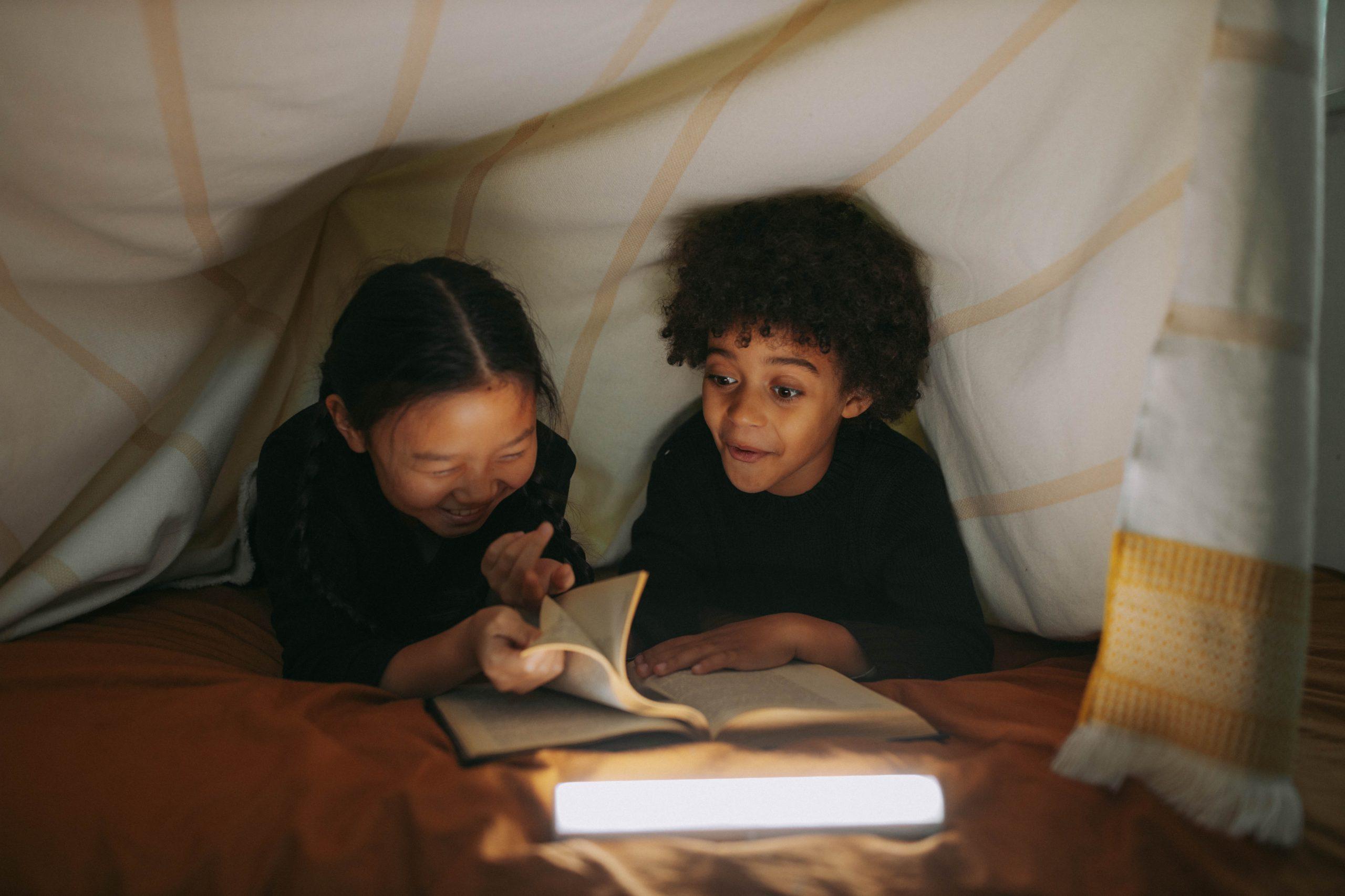 Menina e menino lendo livros em uma cabana infantil