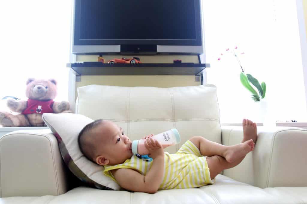 Na foto um bebê deitado em um sofá bebendo leite em uma mamadeira.