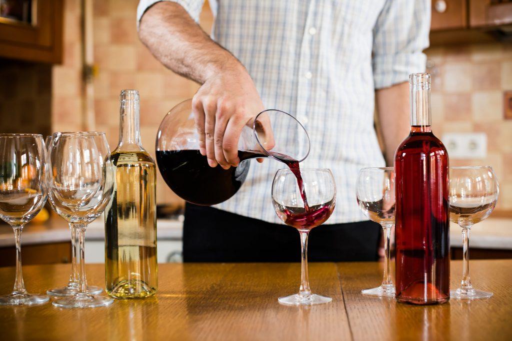 Homem servindo taça de vinho tinto por um decantador.