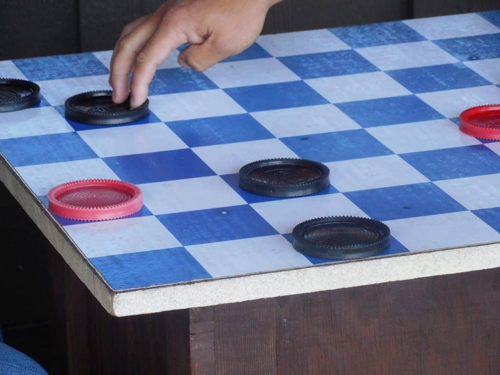 Imagem mostra um tabuleiro e peças de damas do tamanho de uma pequena mesa.