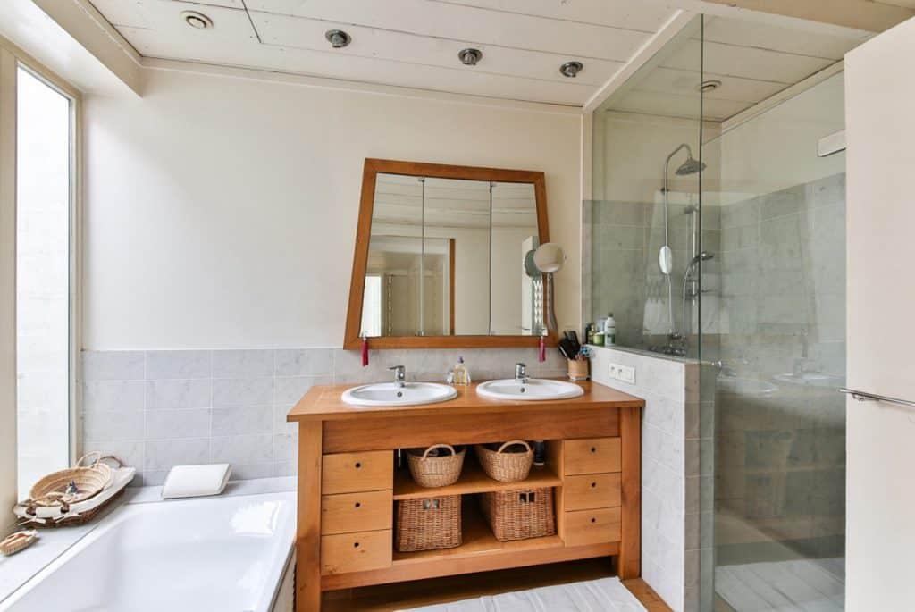 Banheiro bem iluminado e espaçoso. À esquerda há uma banheira branca, à direita um box e no meio há um móvel de madeira com duas pias e, acima, um espelho em formato de trapézio.