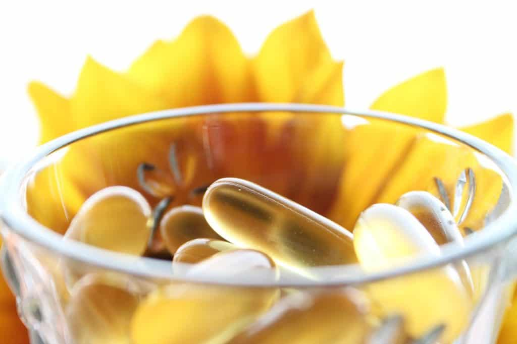 Imagem mostra em primeiro plano o topo de um copo, cheio de cápsulas. Ao fundo, silhuetas de folhas.
