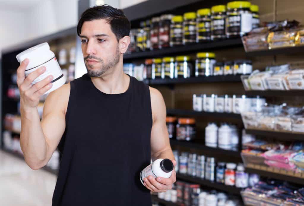 Imagem de um homem lendo o rotulo de um suplemento e outro pote na mão em uma loja de suplementos.