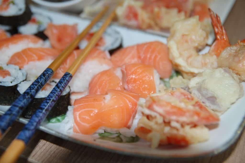 Imagem de um hashi de bambu em cima de um prato de comida oriental.