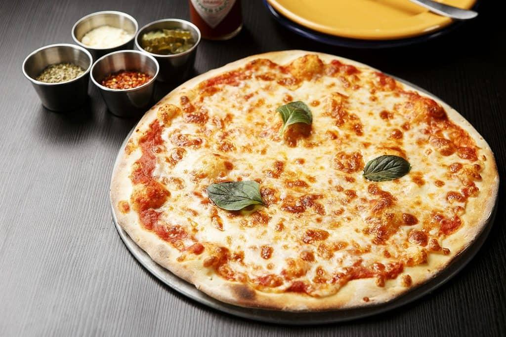 Imagem de pizza de queijo em cima de pedra.
