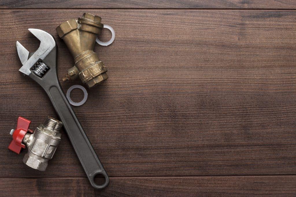 Uma chave inglesa entre duas torneiras desinstaladas.