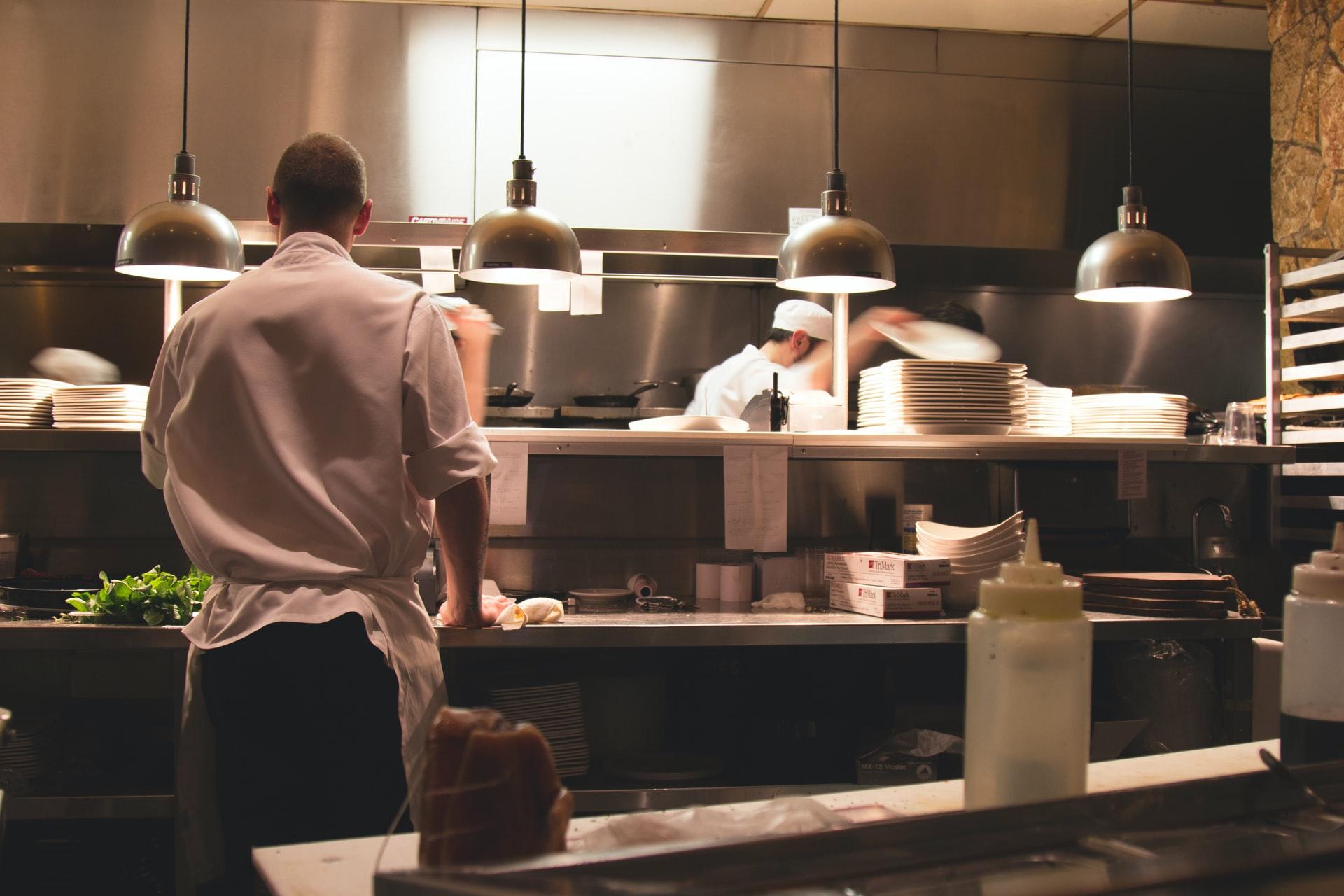 Na foto uma cozinha industrial com uma pessoa de costas.