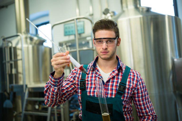 Um homem com óculos de proteção segurando um densímetro na frente de um fermentador.