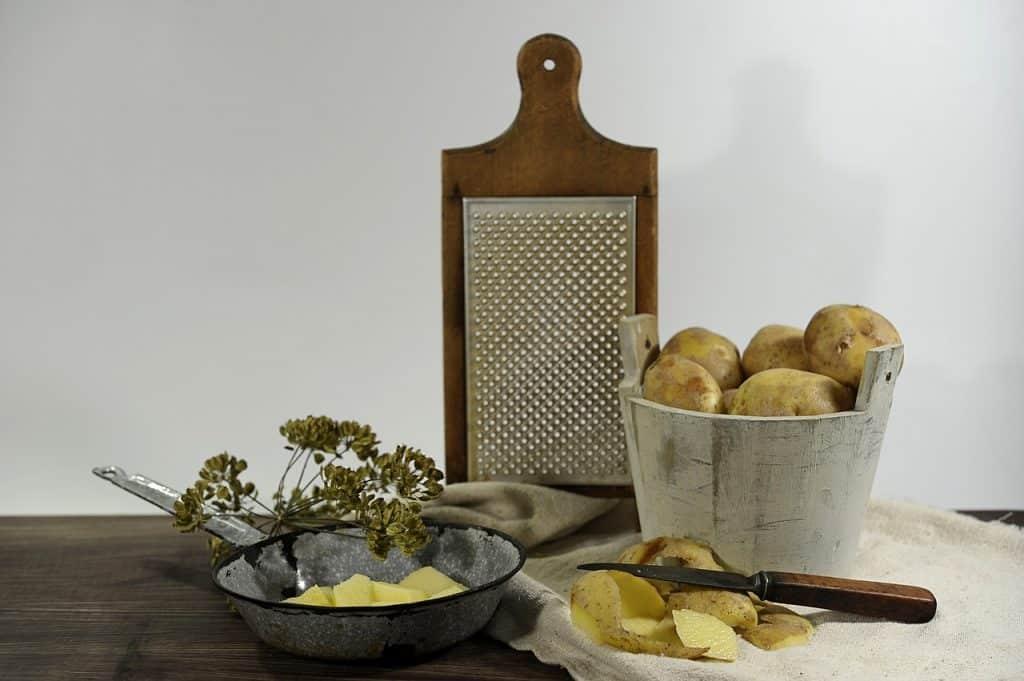 Ralador com estrutura de madeira próximo a recipiente com batatas.