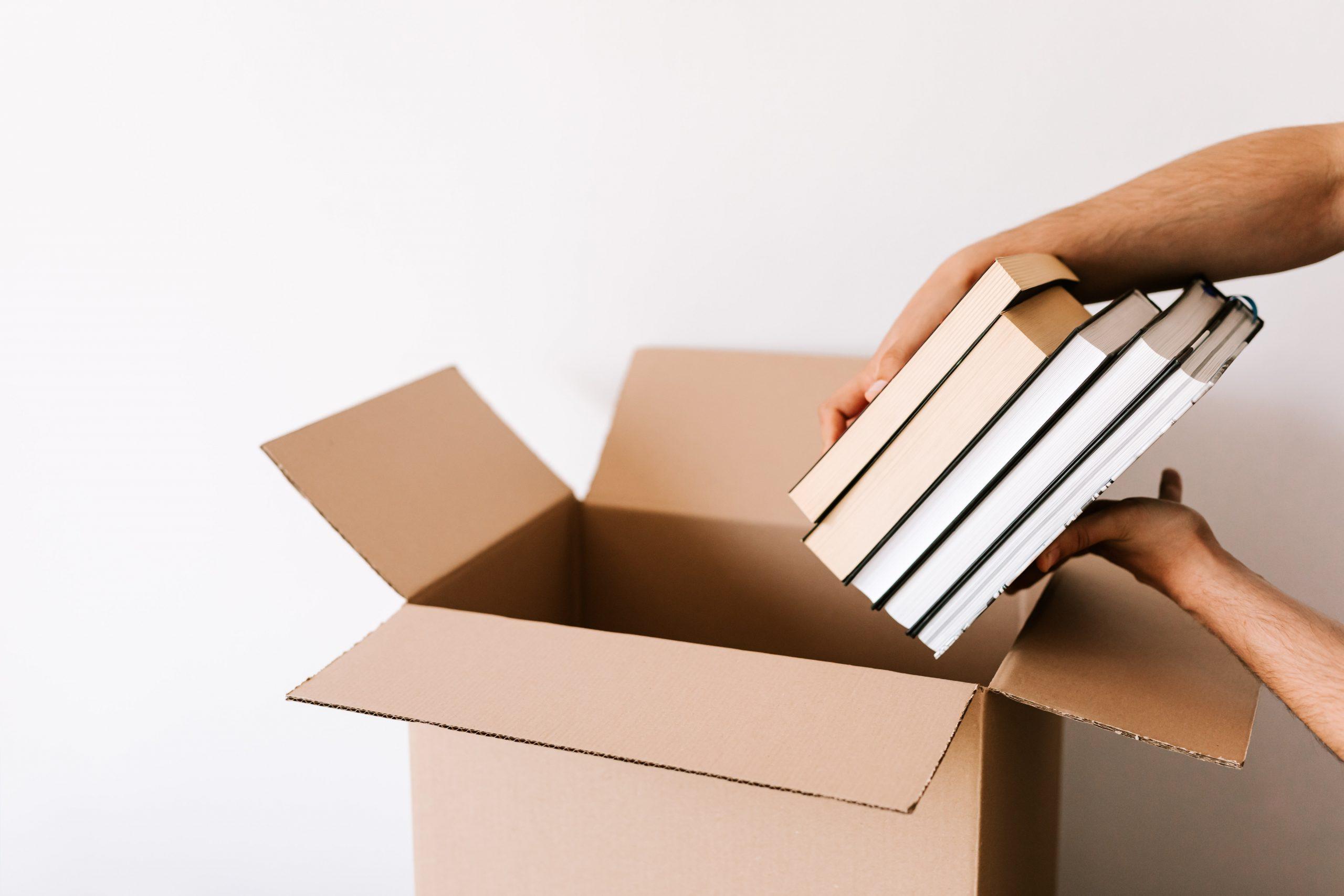 Pessoa colocando livros na caixa de papelão